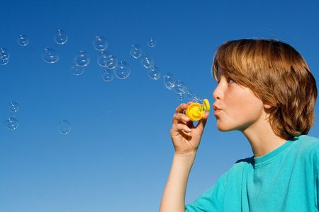 by blowing: happy child blowing bubbles playing outdoors