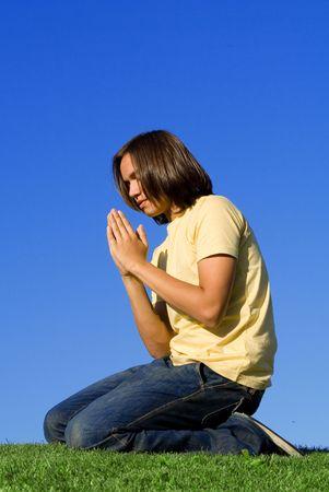 young man praying outdoors photo