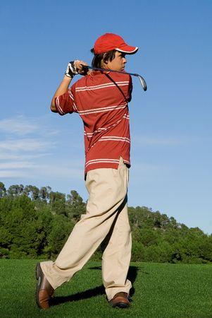teen golf: ni�o jugando al golf