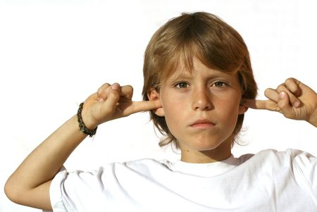 defiant child with fingers in ears