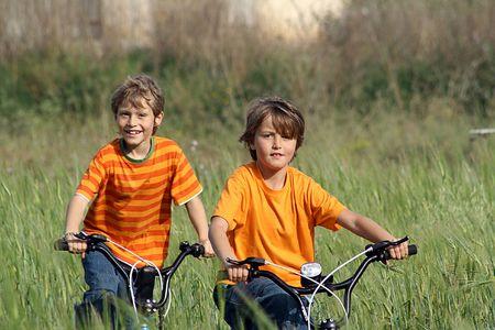 gemelas: ni�os en bicicletas  Foto de archivo