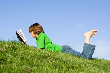 tween boy: child reading book outside