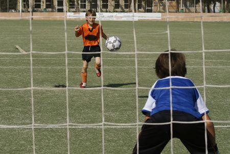 jugando futbol: Chicos j�venes jugando f�tbol  Foto de archivo