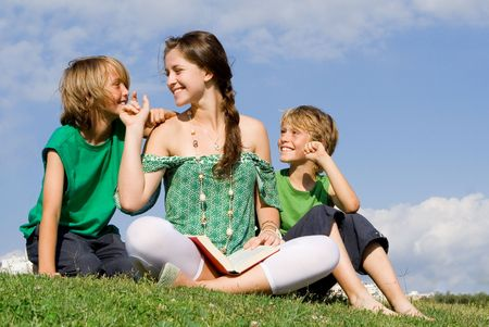 mother and children reading book or bible outdoors