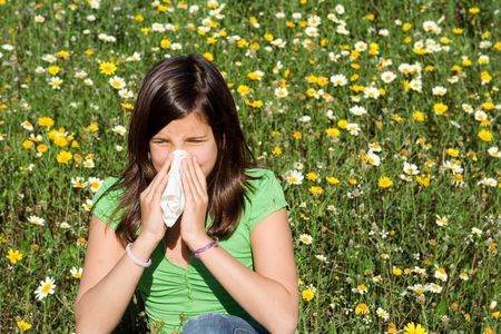 hayfever: child blowing nose of sneezing with hayfever allergy