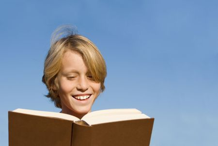 young boy reading book or bible