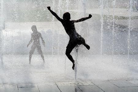 boy jumping: ni�o feliz jugando en fountaing  Foto de archivo