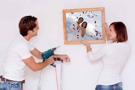 putting up: putting up picture in frame(photo in frame is mine of same couple9 Stock Photo