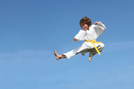 defense: young boy doing karate kick Stock Photo