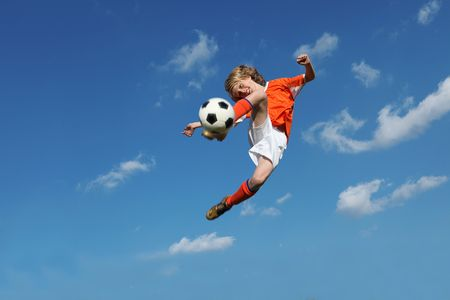 boy playing football kicking ball photo