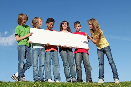 tweens: group of diverse kids with blank sign Stock Photo