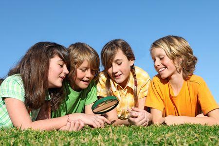 campamento de verano: grupo de ni�os jugando con lupa
