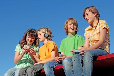 preadolescentes: grupo de ni�os jugando con los dispositivos electr�nicos Foto de archivo