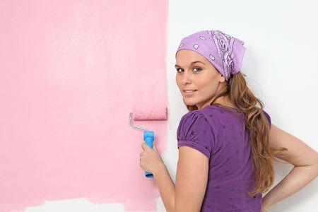 woman painting nursery wall pink Stock Photo