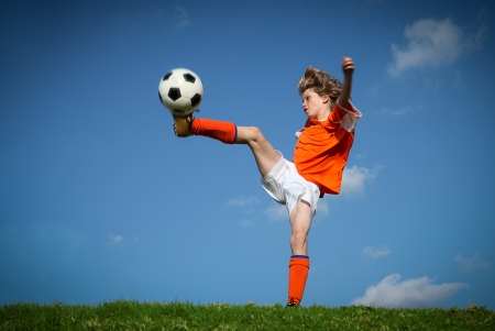 Child kicking playing football. photo