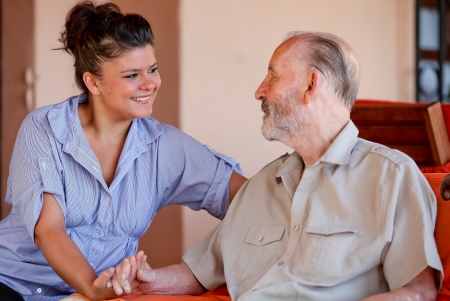 carer: elderly man with nurse carer or granddaughter. Stock Photo