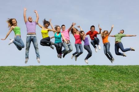 personas saltando: Grupo de campamento de verano de adolescentes jumpingat Foto de archivo