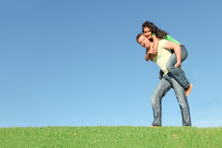 piggy back: happy smiling couple outside on grass giving piggy back in summer Stock Photo