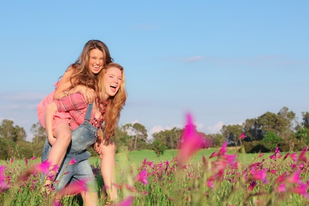 bff: happy smiling spring or summer piggy back teens or teenager kids Stock Photo