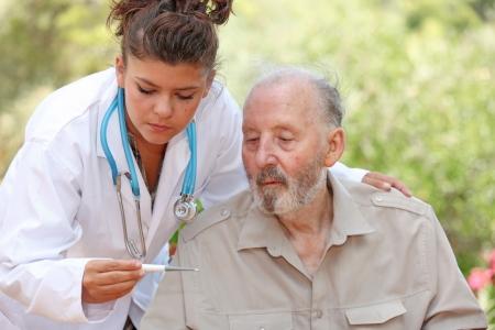 senior home: nurse or doctor taking temperature of senior ill patient