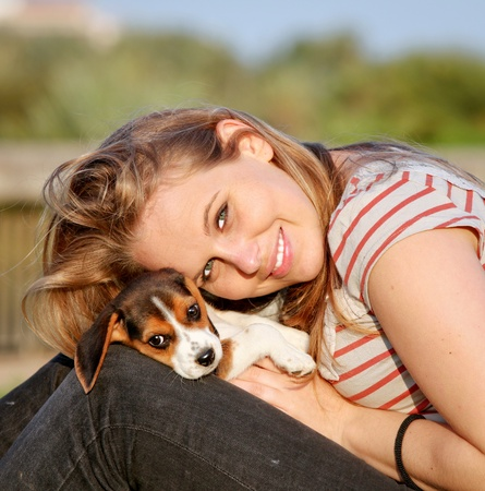 happy young woman with her pet beagle puppy dog outside photo