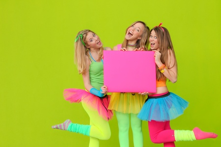 neon color: happy party teen girls in neon fancy dress clothing with blank board
