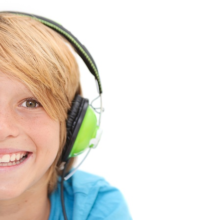 Half face of smiling happy boy listening to music with earphones Stock Photo
