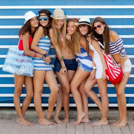 adolescentes chicas: grupo diverso de las ni�as van a la playa de vacaciones de verano