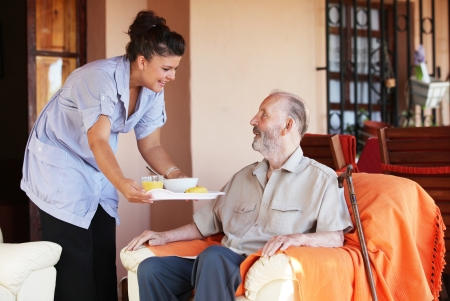 carer: elderly senior being brought meal by carer or nurse