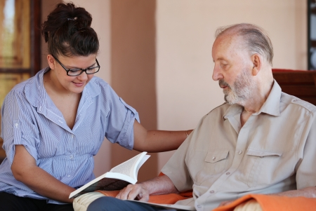 care at home: carer reading to senior