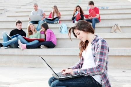 students working with laptops and books on campus photo