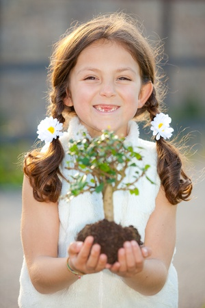 girl holding tree as invironmental or nature concept ( focus on child ) photo