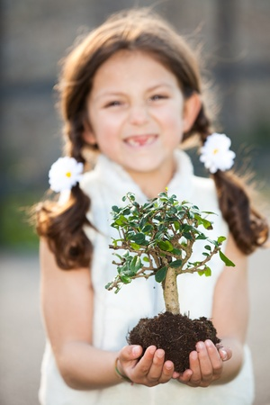 caring for: child caring for the invironment (focus on tree) Stock Photo