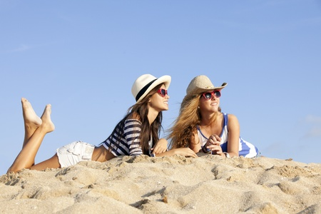 girls laying in sand on summer vacation photo