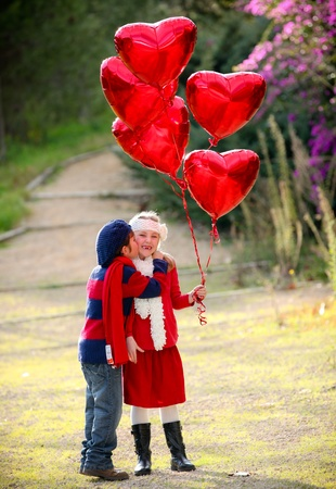 valentines kids with gift of balloons and kiss photo