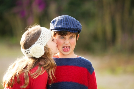 first love: little girl giving kiss to young embarrassed boy. Stock Photo