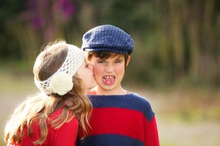 personas besandose: ni�a da un beso a la joven avergonzada joven. Foto de archivo