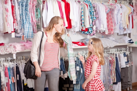 kids dress: mother and child shopping choosing dress in clothes shop