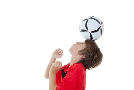 young boy soccer or football player balancing ball on head photo