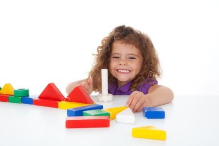 young happy girl child playing with building bricks or blocks Stockfoto
