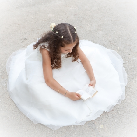 first communion or confirmation, child reading bible or prayer book photo