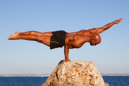 balanza: equilibrar equilibrio hombre fuerte en la roca. Foto de archivo