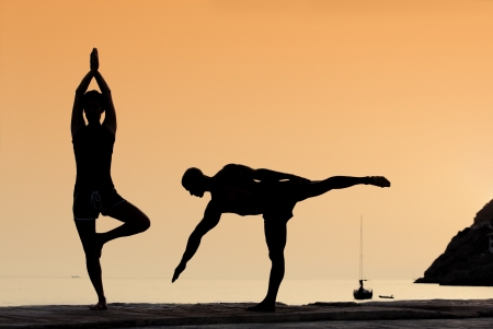 healthy couple doing yoga exercises outdoors
