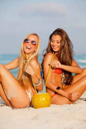 junge Frauen trinken am Strand Sommer Urlaub oder Urlaub Lizenzfreie Bilder