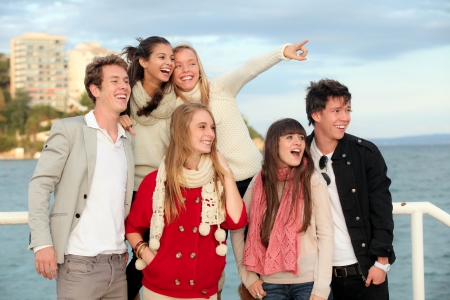 group of happy surprised teens or young people pointing and smiling  photo