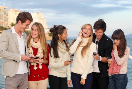 group of happy smiling teens, kids, texting and calling with mobile or cell phones