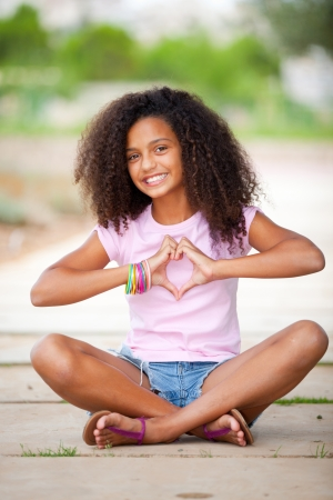 young happy smiling african american black  teen girl with afro hair making heart shape