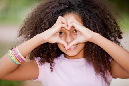 jungen glücklich lächelnde schwarze Mädchen machen Herzform