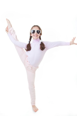 Happy smiling child gymnast exercising or dancing photo