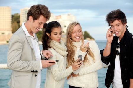 teens talking or texting on mobile cell phones  photo